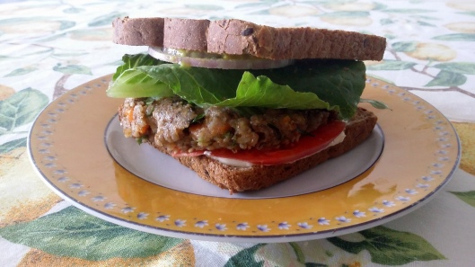 Kasha burger with vegan mayo, organic mustard, tomato, romaine lettuce leaf, sliced red raw onion, toasted multi-seeds dark grain bread.